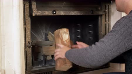 wood burner : 4k video of young man opening fireplace glass door and putting wooden logs inside Stock Footage