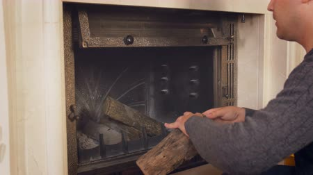 popel : 4k video of young man throwing wooden logs inside of fireplace at house Dostupné videozáznamy