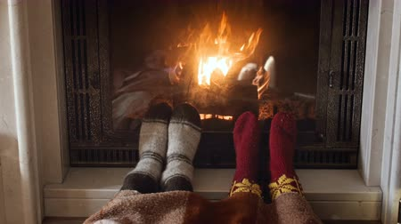pletený : 4k footage of two people warming their feet in woolen knitted socks at burning fireplace