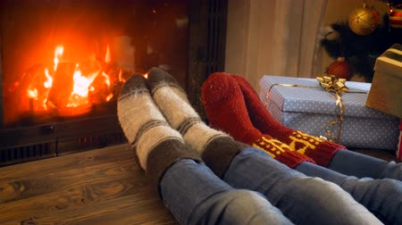 happy socks : 4k video of family in knitted woolen socks resting next to Christmas tree at burning fireplace Stock Footage