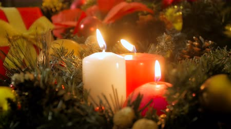 освещенный : Closeup 4k video of three burning candles on Christmas eve