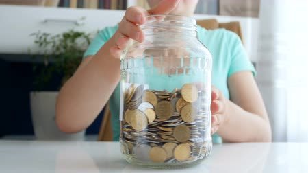 doação : 4k footage of young woman sticking label with New car title on jar full of coins Vídeos