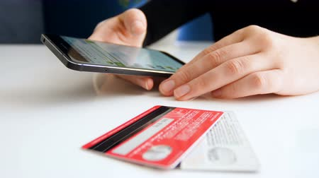 účty : Closeup footage of young woman browsing online stores on smartphone. Two credit cards lying on table next to her.