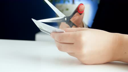 konkurzu : Closeup 4k footage of female bank worker cutting plastic credit card with scissors