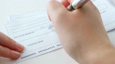 checkbook : CLoseup 4k footage of young woman filling 100 dollar bank cheque for charity purposes