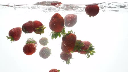 ferahlatıcı : Closeup slow motion footage of lots of raspberries falling and splashing in water against white background Stok Video