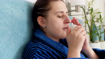 chřipka : Closeup 4k video of young sick woman blowing her nose and using nasal spray