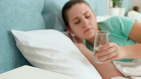 aspirina : 4k footage of young woman with headache lying in bed and drinking water from glass Vídeos