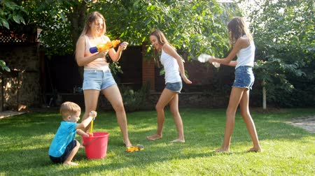 teen age : 4k video of young mother having water guns battle with her children on backyard Stock Footage