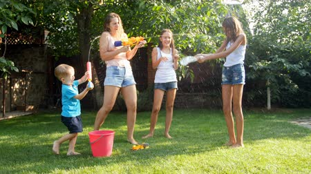squirting : 4k video of happy young family having water guns battle at hot sunny day on grass