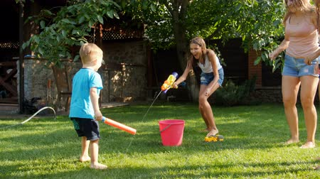 пистолеты : 4k video of happy elder sister having water battle on toy guns with her little toddler brother Стоковые видеозаписи
