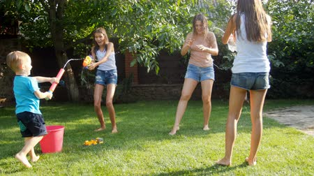 пистолеты : 4k footage of happy family having fun on grass at backyard and shooting with water from toy guns
