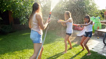 squirting : 4k video of laughing happy family playing with garden hose and water guns at house backyard