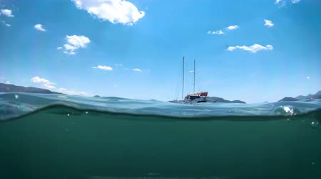 4k underwater video of luxurious yacht and boat moored in sea next to the shore Vídeos