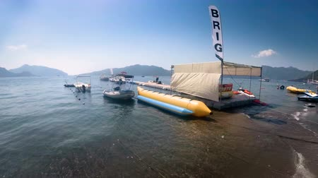 4k footage of inflatable banana, scooters and boats moored at sea pontoon bridge
