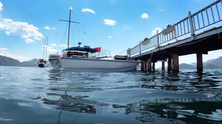 4k video from the sea level on moored yacht and boat at wooden pier