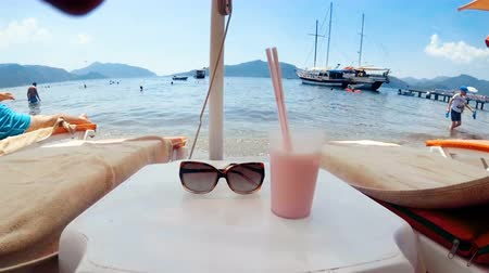 4k closeup footage of sunglasses and cocktail with two straws on table between sunbeds on sea beach