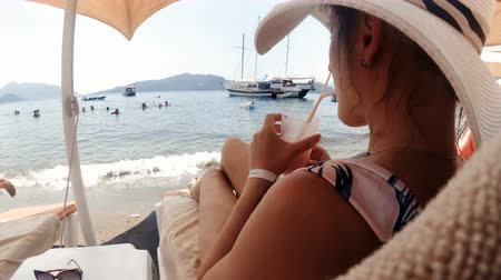 Toned closeup video of beautiful young woman in hat relaxing on beach and drinking cocktail Vídeos