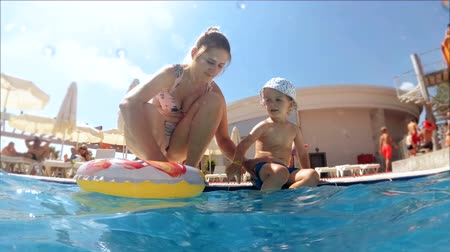 Video of toddler boy with mother sitting on the polside at aquapark Vídeos