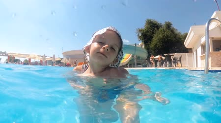 Slow motion video of happy smiling young woman with her toddler son in swimming pool at hotel resort