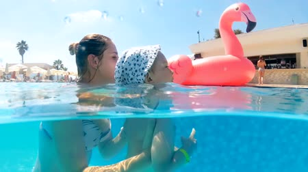 Slow motion underwater video of cheerful smiling mother with son swimming in pool at hot sunny day Vídeos