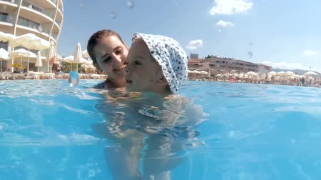 Slow motion underwater video of smiling young woman with toddler boy swimming in outdoor pool at hotel resort on hot sunny day