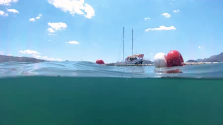 Slow motion underwater footage moored yachts in sea at bright sunny day