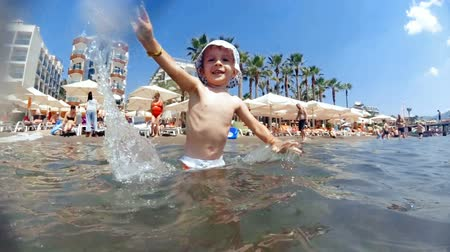 Slow motion video of happy laughing toddler boy splashing with sea water on beach Vídeos