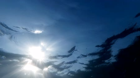 Slow motion underwater video of looking up at the bright sun light from sea bottom Vídeos