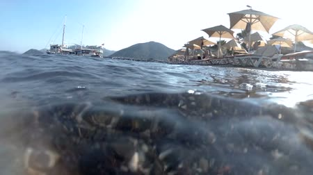 Closeup slow motion video of sea wave with sand, rocks and weeds rolling over the shore with sunbeds and sunshade umbrellas