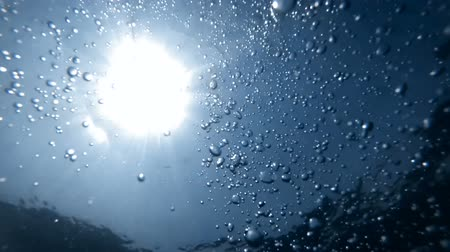 Slow motion underwater video from the sea bottom on floating air bubbles in sun light rays