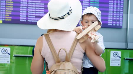 4k video of young mother holding her little boy playing with wooden toy airplane at airport terminal Vídeos
