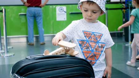assentos : 4k video of little toddler boy playing with toy wooden airplane in check-in line at airport Vídeos