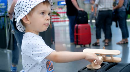 assentos : 4k footage of little toddler boy playing with wooden toy airplane before flight on plane from airport terminal Vídeos