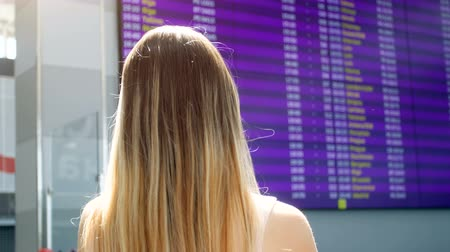 Rear view 4k video of young woman with long hair looking at display with time of aircraft departures at international airport terminal