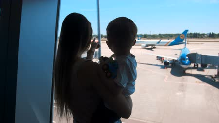Closeup 4k footage of mother and child silhouettes looking at landing airplanes in international airport through big window