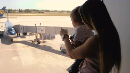 tourist silhouette : 4k footage of oyung mother with toddler son looking at jet airplanes on runway at international airport terminal