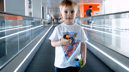 winda : 4k video of smiling toddler boy with toys standing on travalator at international airport terminal