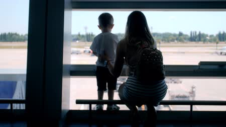 4k video of young mother with little toddler boy lookin at airplanes on runway at international airport terminal