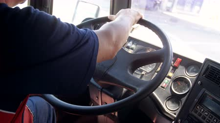 Closeup 4k footage of driver of public bus turning steering wheel