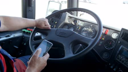 řidič : Closeup 4k footage of public bus driver typing message on smartphone and talking by phone. Concept of irresponsible driver and danger on road Dostupné videozáznamy