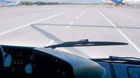 4k footage of bus with passengers riding to airplanes on airport runway