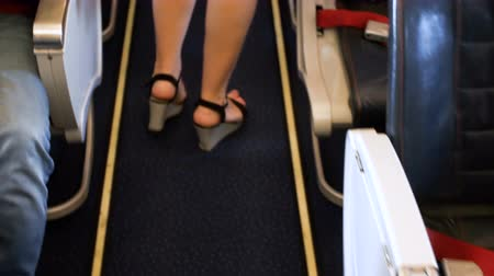 Closeup 4k footage of female feet walking between rows of seats at passenger airplane