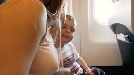 4k video of young mother kissing and hugging her little toddler son in airplane during flight
