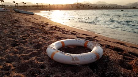 boa : 4k footage of life saving ring lying on the sandy beach at sunset