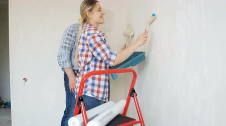 obnova : Video of young man with his wife painting walls with white paint in new house