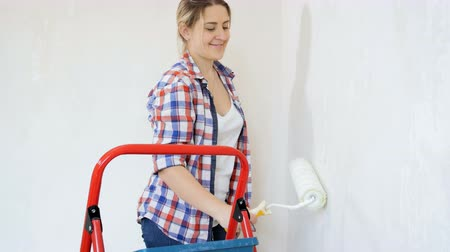 renovar : Beautiful young woman renovaating her new apartment. Young girl painting walls at her room