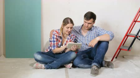 catalog : 4k footage of young family choosing new furniture for their new house. Couple sitting on floor and using tablet computer in their apartment under renovation