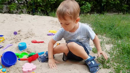 sandpit : 4k footage of cute toddler boy playing in the sandbox on playground at park