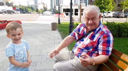 bank : 4k video of grandfather with grandson launching toy helicopter on bench at park
